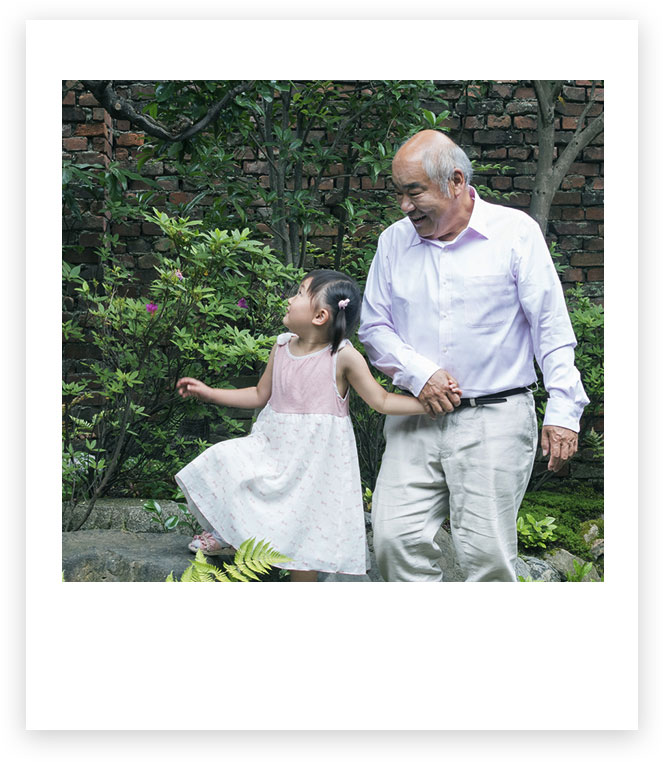 Grandfather and granddaughter hold hands outside